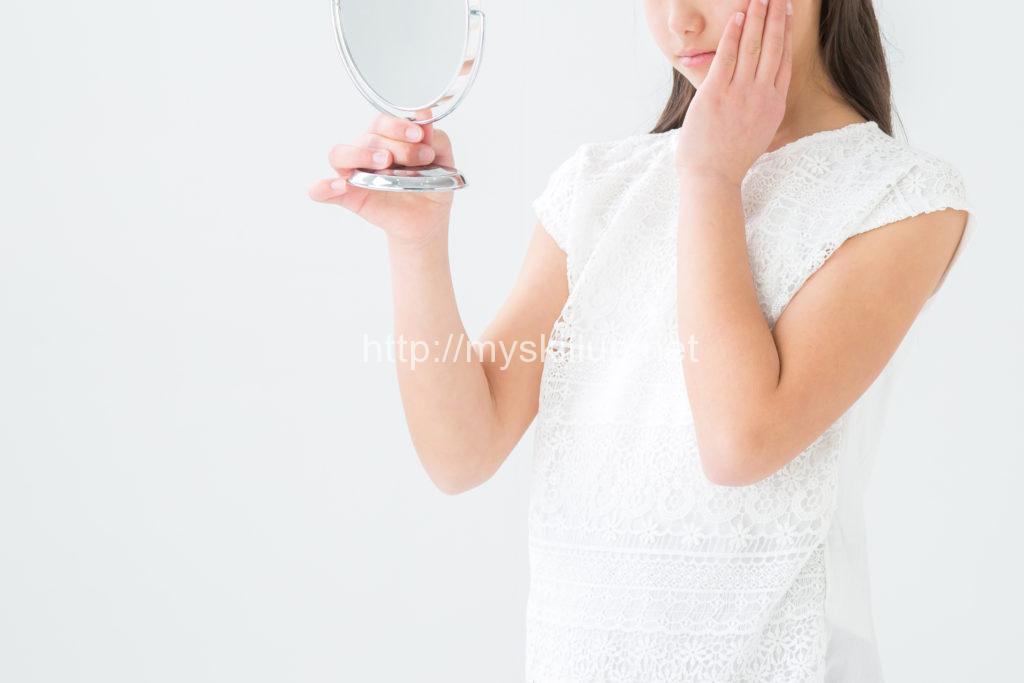 鏡を見ながら困った様子の女性