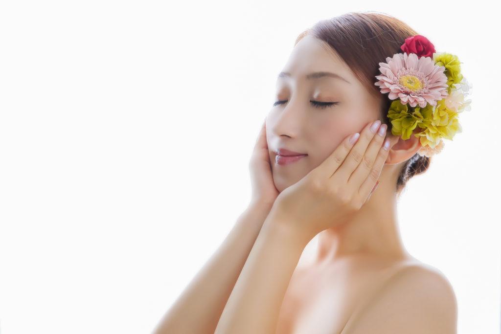 頬を両手で覆うキレイな花の髪飾りを付けた女性