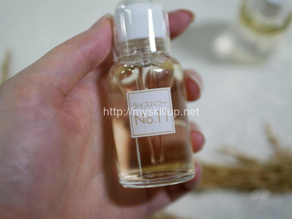 ライスパワーNo.11の原液入りの瓶を持つ左手